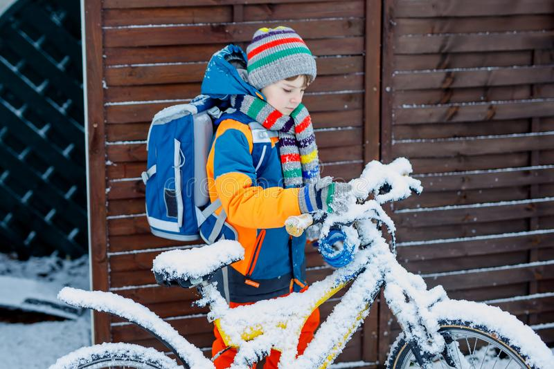 Poco muchacho del niño de la escuela de la clase elemental que camina a la escuela durante las nevadas niño que quita nieve de la fotos de archivo