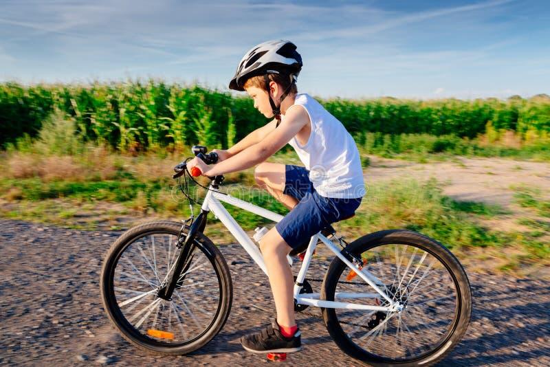 Poco muchacho del niño en el casco blanco que monta su bicicleta fotografía de archivo