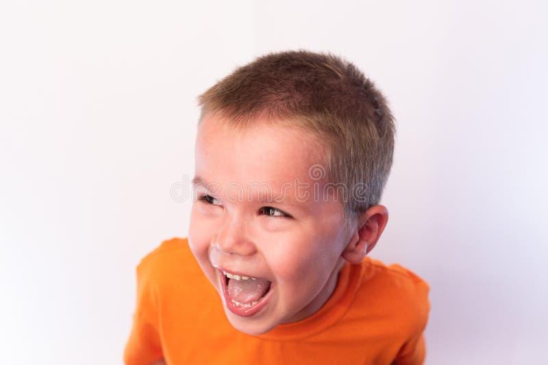Poco muchacho lindo en una camiseta brillante, riendo feliz contra un fondo brillante foto de archivo
