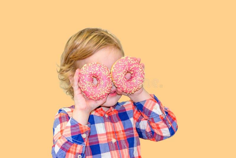 Poco muchacho lindo feliz está comiendo el buñuelo en la pared amarilla del fondo imagen de archivo