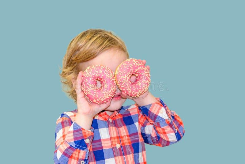 Poco muchacho lindo feliz está comiendo el buñuelo en la pared azul del fondo imagenes de archivo