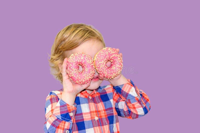 Poco muchacho lindo feliz está comiendo el buñuelo en la pared púrpura del fondo imagen de archivo libre de regalías