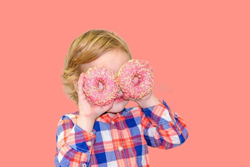 Poco muchacho lindo feliz está comiendo el buñuelo en la pared rosada del fondo fotos de archivo