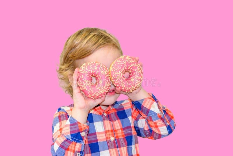 Poco muchacho lindo feliz está comiendo el buñuelo en la pared rosada del fondo imágenes de archivo libres de regalías