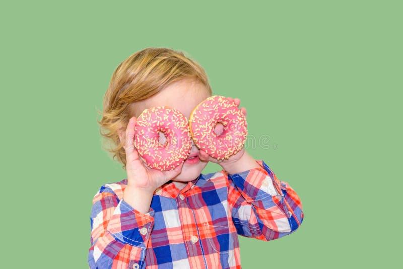 Poco muchacho lindo feliz está comiendo el buñuelo en la pared verde del fondo fotografía de archivo