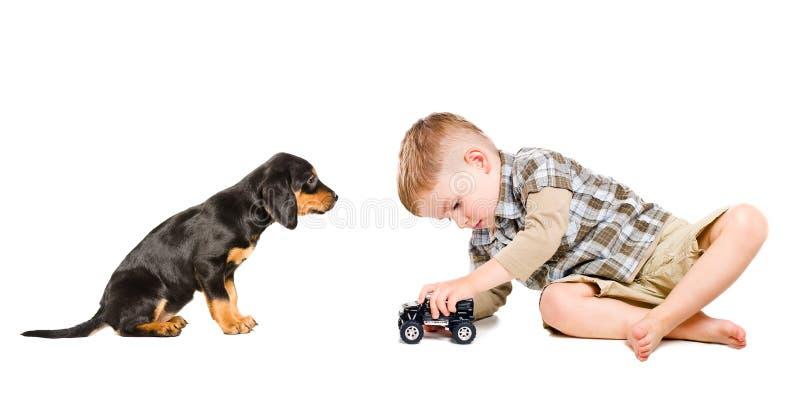 Poco muchacho lindo juega un coche del juguete con su perrito imagen de archivo libre de regalías