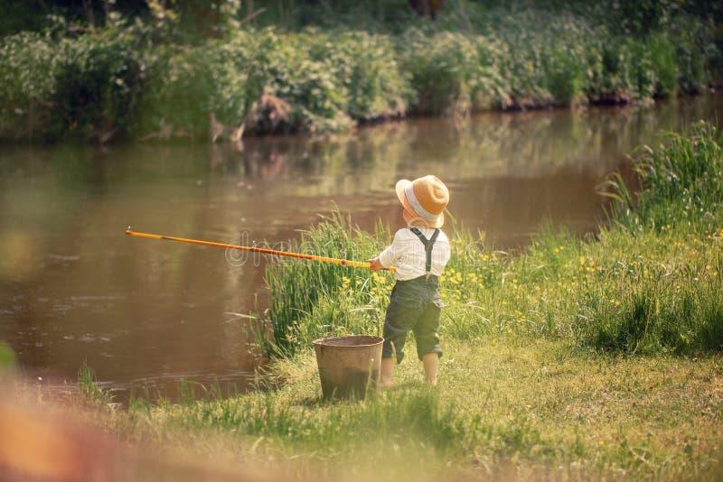 Poco muchacho lindo que pesca en un lago en un día de verano soleado El cabrito está jugando foto de archivo libre de regalías