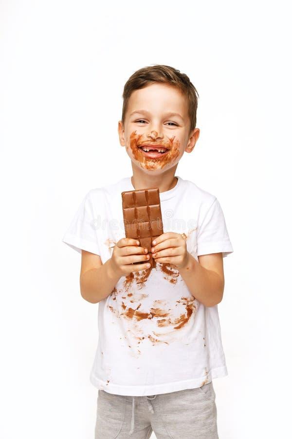 Poco muchacho sucio está comiendo el tiro del estudio del chocolate imagenes de archivo