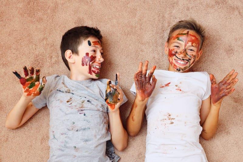 Poco muchachos alegres con la pintura en la cara y las manos que mienten en piso y la risa imagen de archivo libre de regalías