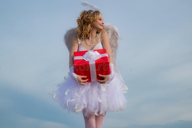 Poco ?ngel en amor Dios del amor Hada real de historias m?gicas Ni?o encantador Ángel del cupido con el regalo en tarjeta del día fotos de archivo