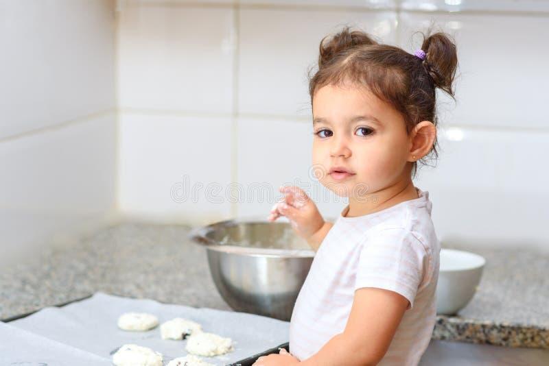 Poco ni?a peque?a que hace la panader?a de la torta en cocina foto de archivo