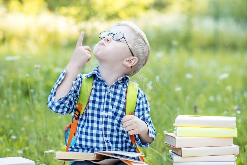 Poco niño divertido sube con nuevas ideas El concepto de aprendizaje, de escuela, de mente, de forma de vida y de éxito imagen de archivo