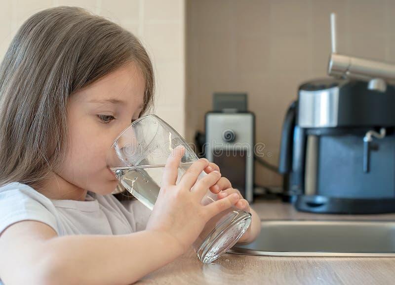 Poco niño está bebiendo el agua potable en casa, cierre para arriba Tomar cuidado de propia salud Concepto de forma de vida sana, foto de archivo