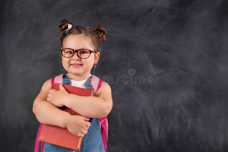 Poco niño lindo que sostiene los libros en la pizarra Concepto de la educaci?n foto de archivo