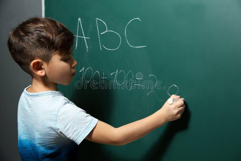 Poco niño que escribe letras y que hace matemáticas en la pizarra imágenes de archivo libres de regalías