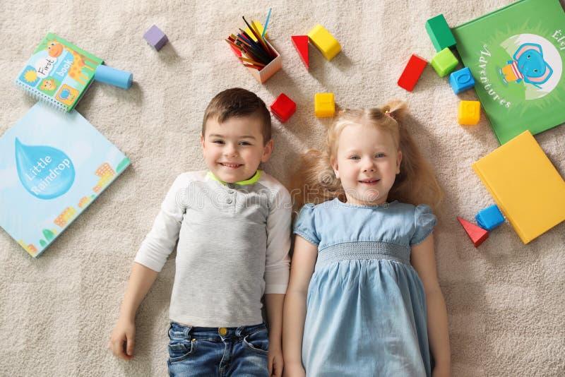 Poco niños con los juguetes y los libros que mienten en la alfombra dentro playtime fotos de archivo