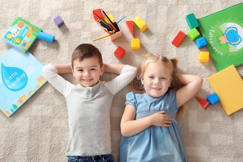 Poco niños con los juguetes y los libros que mienten en la alfombra, visión superior playtime foto de archivo libre de regalías