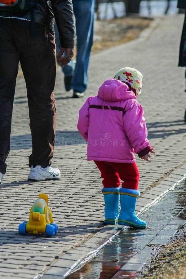 Poco niños que caminan alrededor de parque de la primavera El entretenimiento del niño en primavera temprana fotos de archivo