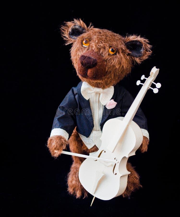 Poco oso de peluche que toca el violoncelo fotos de archivo