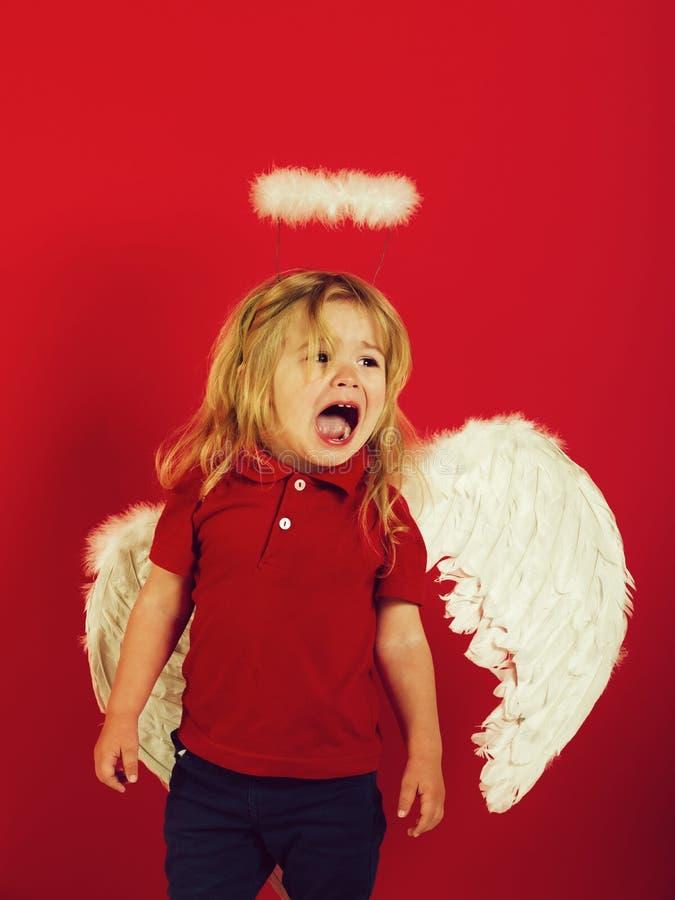 poco ragazzo di angelo che grida con le ali e l'alone della piuma bianca immagini stock libere da diritti