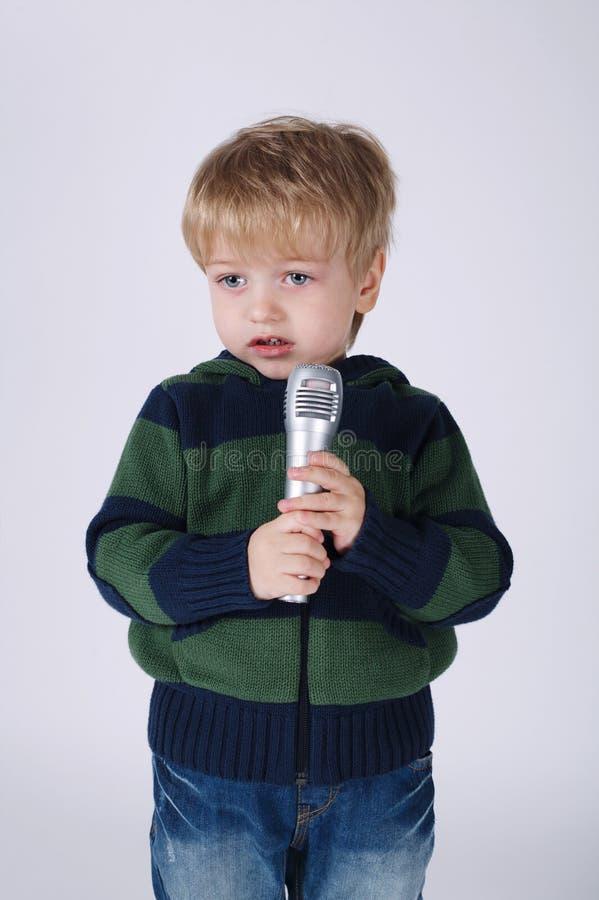 Poco ragazzo di canto con il mic fotografia stock libera da diritti