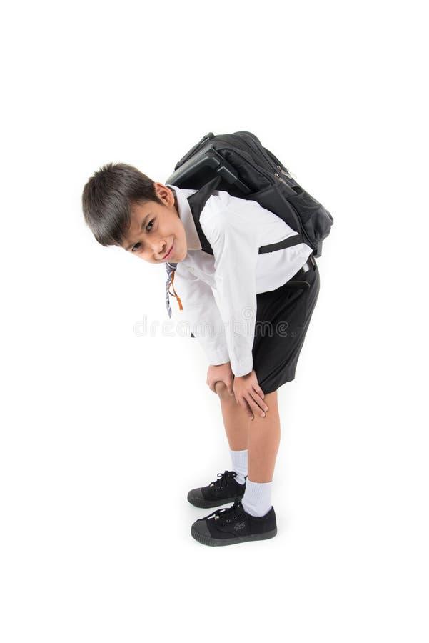 Poco ragazzo di scuola che prende borsa pesante in pieno dei libri immagine stock