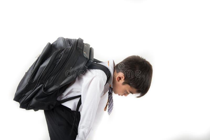 Poco ragazzo di scuola che prende borsa pesante in pieno dei libri fotografia stock