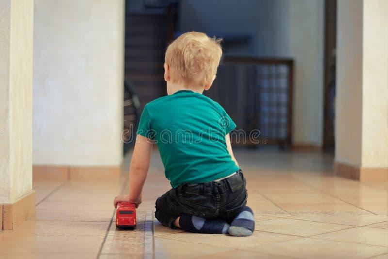 Poco solamente bebé caucásico con el pelo justo se sienta en el piso, de nuevo al espectador, con el juguete rojo del autobús Con fotos de archivo