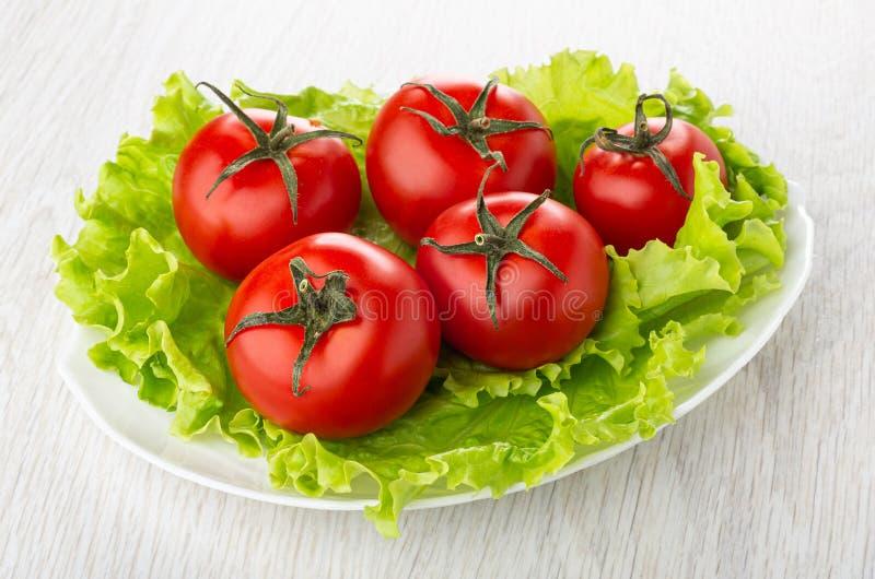 Pocos de tomates rojos en las hojas de la lechuga en plato en la tabla de madera fotos de archivo libres de regalías
