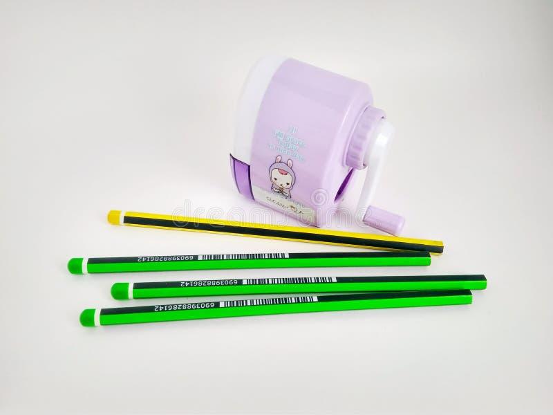 Pocos lápices y sacapuntas mecánicos en blanco fotos de archivo