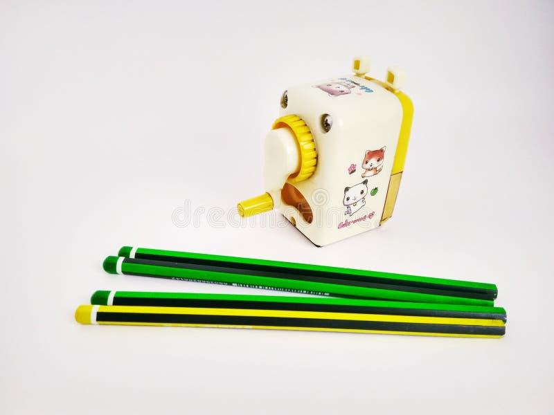 Pocos lápices y sacapuntas mecánicos en blanco fotografía de archivo libre de regalías