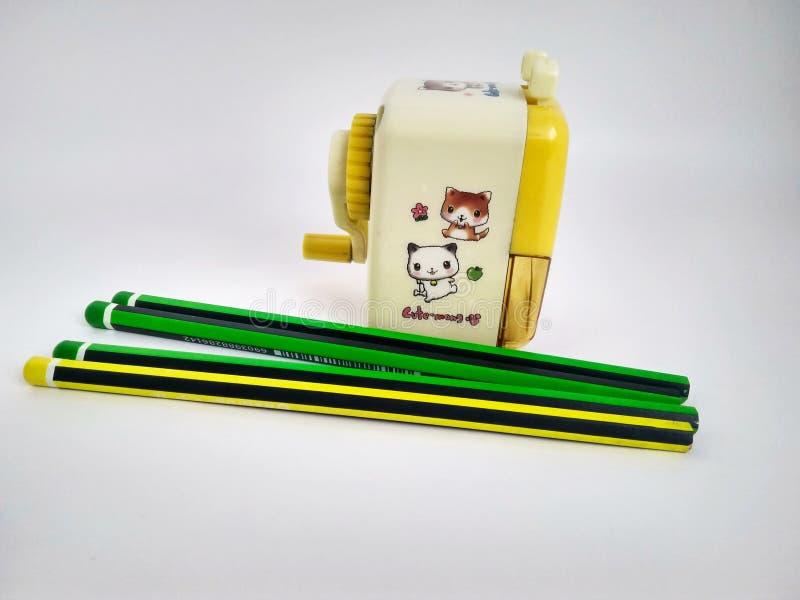 Pocos lápices y sacapuntas mecánicos en blanco foto de archivo