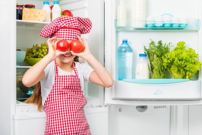 Pocos tomates del holdin de la muchacha del cocinero como ojos foto de archivo