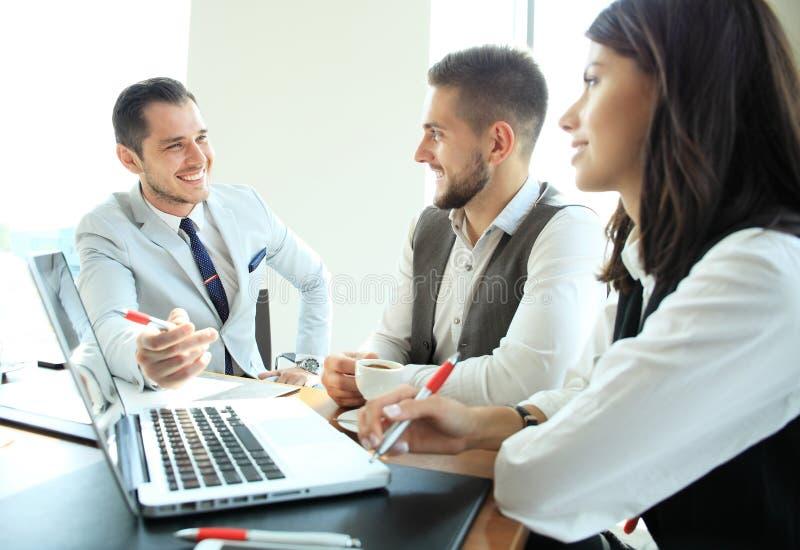 Początkowa biznes drużyna na spotkaniu w nowożytnym jaskrawym biurowym wewnętrznym brainstorming, pracujący na laptopu i pastylki zdjęcia royalty free