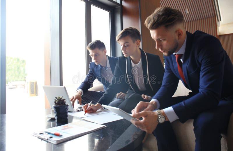 Początkowa biznes drużyna na spotkaniu w nowożytnym jaskrawym biurowym wewnętrznym brainstorming, pracujący na laptopu i pastylki fotografia royalty free