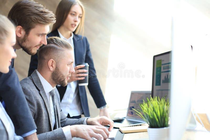 Początkowa biznes drużyna na spotkaniu w nowożytnym jaskrawym biurowym wewnętrznym brainstorming, pracujący na pastylce i pecetów obraz stock