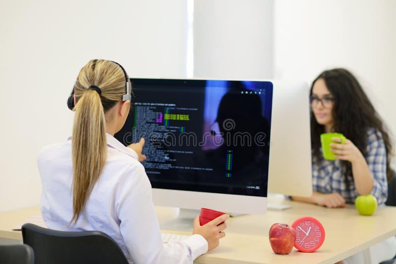 Początkowy biznes, młoda kobieta jako deweloper oprogramowania pracuje na komputerze przy nowożytnym biurem zdjęcie stock
