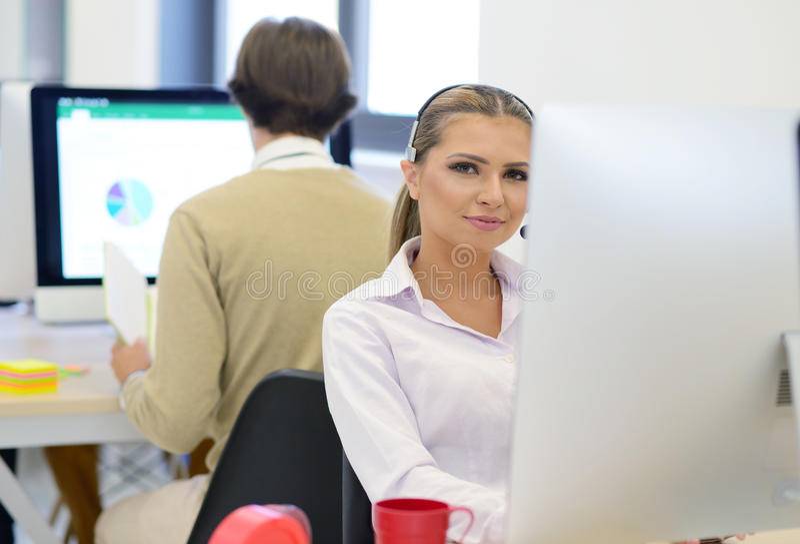 Początkowy biznes, młoda piękna kobieta jako deweloper oprogramowania pracuje na komputerze przy nowożytnym biurem fotografia stock