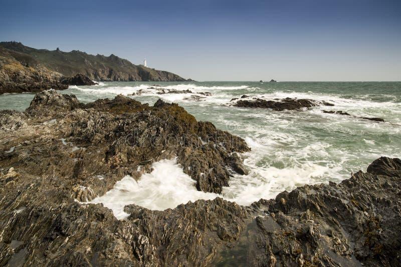 Początku punktu latarnia morska w skalistym niewygładzonym morze krajobrazie w Cornwa zdjęcie stock