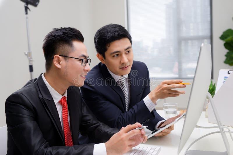 Pocz?tkowi partnery biznesowi pracuje wp?lnie w desktop zdjęcia stock