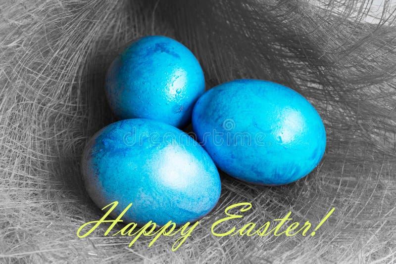 Pocztówka z Trzy Błękitnymi Wielkanocnymi jajkami na szarość fotografia stock