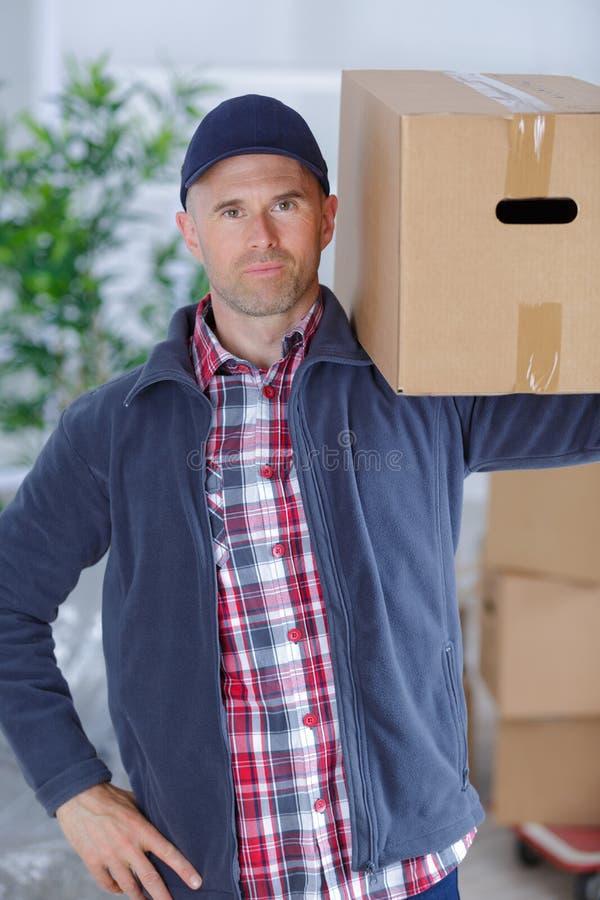 Poczta doręczeniowy pojęcie - uśmiechnięty mężczyzna przewożenia kartonu pudełko zdjęcie royalty free