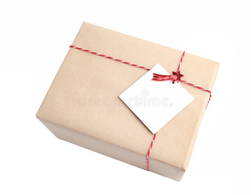 Poczta pakuneczek zawijający z rzemiosło brown papierem z czerwonym dratwy isolat zdjęcia royalty free