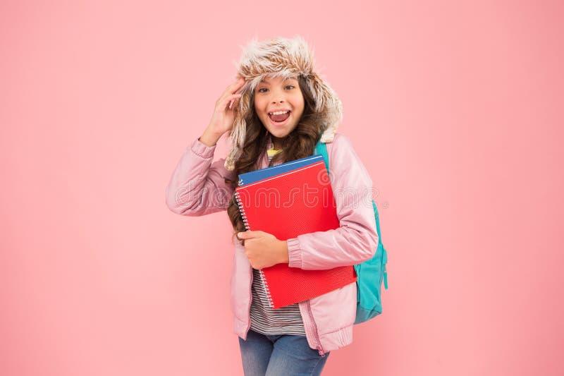Poczuj ducha wakacje zimowe i wakacje dziecko ciepłe ubrania różowe tło życie codzienne uczniów plecak dla uczennic obraz stock