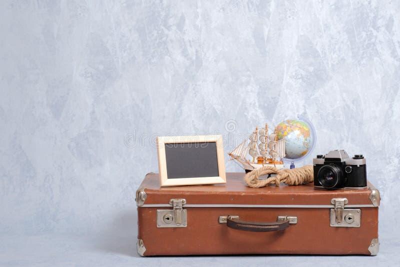 Podława rocznik walizka z lat morskimi akcesoriami na popielatym tle Obrazek rama, kula ziemska, kamera, zabawkarska żaglówka, de obraz stock