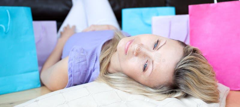 podłogowego łgarskiego zakupy zmęczona kobieta fotografia stock