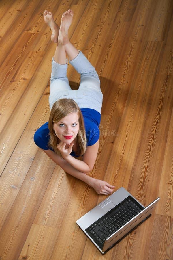 podłogowego laptopu ładna używać kobieta drewniana obraz stock