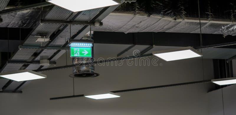 Podświetlany zielony znak awaryjny / gaśniczy z piktogramem dla biegaczy na dachu przemysłowym obrazy royalty free