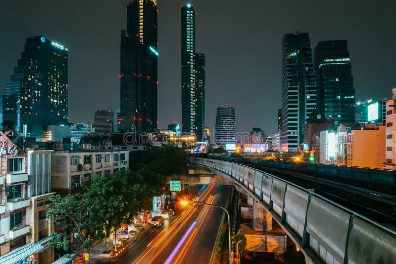 Podświetlenia poruszających się samochodów z wytyczonym w tle biegiem Bangkoku obrazy stock