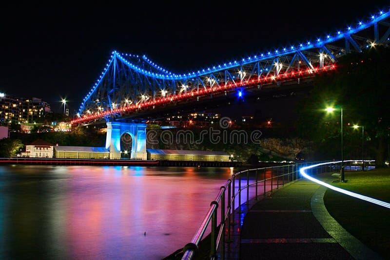 Pod opowieść mosta Brisbane miastem przy nocy czerwony błękitnym, biały i obrazy stock